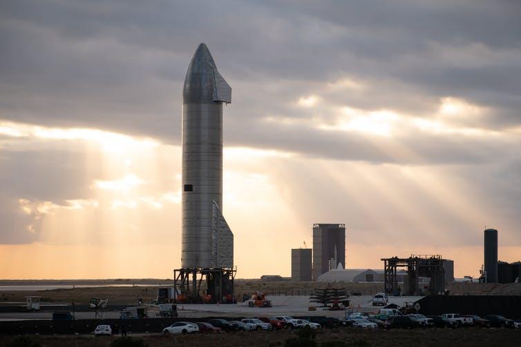 На стартовой площадке вертикально стоит большая серебряная ракета.