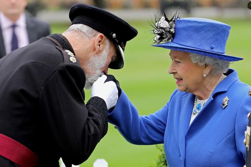 Мужчина в военной форме целует руку королевы в синем пальто и соответствующей шляпе.