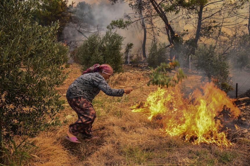 Женщина пытается остановить массовый пожар в селе Какарлар
